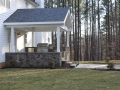 covered porch and outdoor kitchen with stone foundation walls