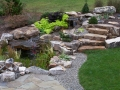 water feature, boulder fire pit, and stone slab steps