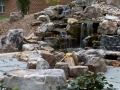 water feature with boulder fire pit and boulder seats